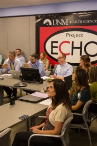 """Surrounding Bouchonville at the Endo ECHO """"hub"""" in Albuquerque are (l to r, at table): UNM endocrinologist Mark Burge, MD; UNM psychiatrist Brant Hagar, MD; nurse manager, Jessica Kirk; clinic coordinator Leena Matib; Endo ECHO CHW trainer, Vanessa Acosta; Project ECHO's Melissa Meier (seated in back are pharmacy students)."""