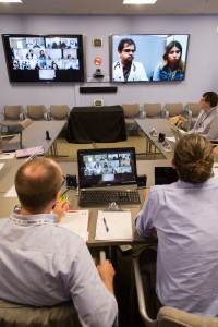Bouchonville listens to a case presentation by Ninad Shet, MD (on screen) of La Casa Family Health Center in Roswell, N.M. On the left screen are primary care clinicians connecting to the teleclinic from across the state.
